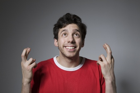 Young man in red top looking up with fingers crossed Stock Photo - 12738257