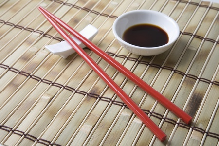 Red chopsticks and side bowl of soy sauce Stock Photo - 12738264