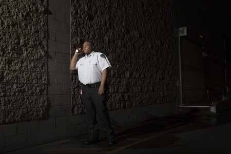 night shirt: Security guard patrols at night with torch