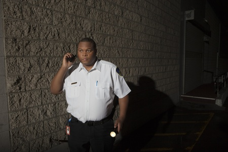 security uniform: Security guard patrols with torch