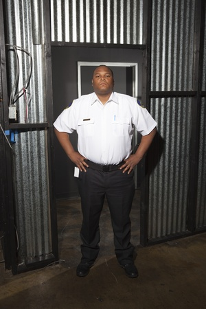 Security guard stands at corrugated metal doorway Stock Photo - 12736346
