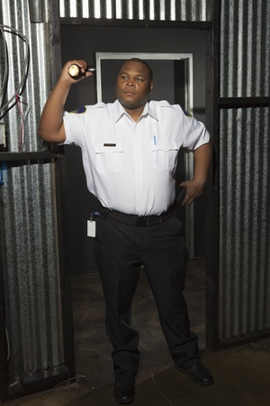 Security guard stands at corrugated metal doorway with torch Stock Photo - 12735514