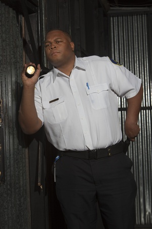 Security guard investigates with torch