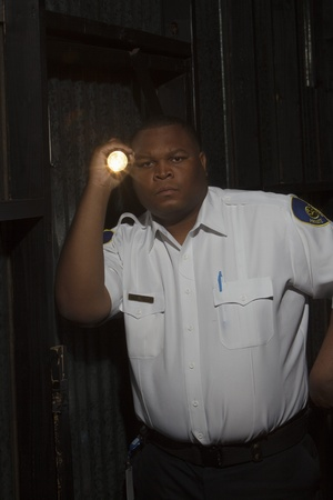investigates: Security guard investigates with torch