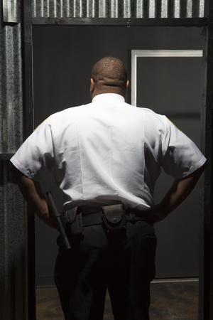 Security guard stands with hands on hips rear view Stock Photo - 12735340