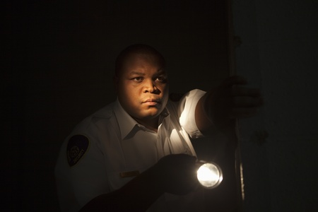 Security guard investigates with flashlight