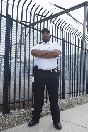 Security guard stands at strengthened prison fence Stock Photo - 12735702