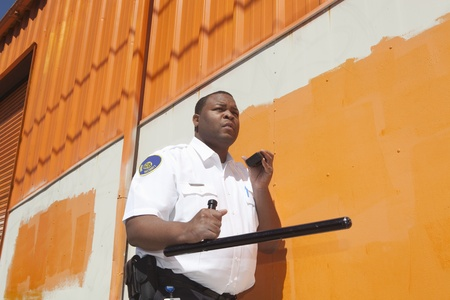 Armed security guard investigates warehouse exterior Stock Photo - 12738270
