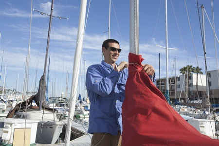 Young man securing sail of boat Stock Photo - 12738285