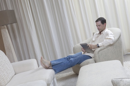 Man sits with feet up reading a digital book Stock Photo - 12738286