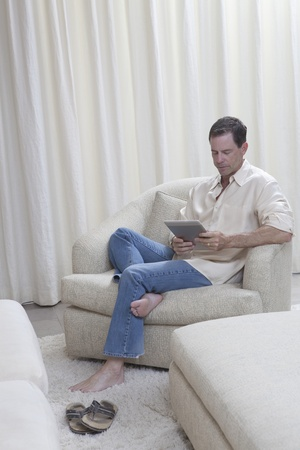 Man sits reading a digital book Stock Photo - 12735343