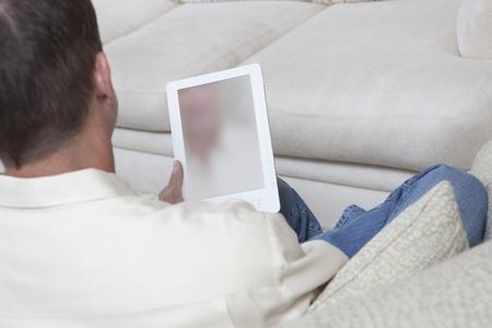 Man sits reading a digital book Stock Photo - 12738288