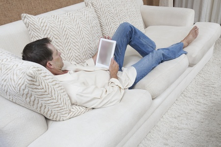 Man sits with feet up reading a digital book Stock Photo - 12738291