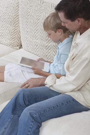 Père et fils assis à lire un livre numérique