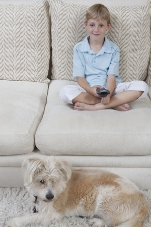 Boy sits on sofa with pet dog watching television Stock Photo - 12738295