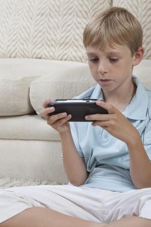 crosslegged: Boys sits cross-legged with portable games console