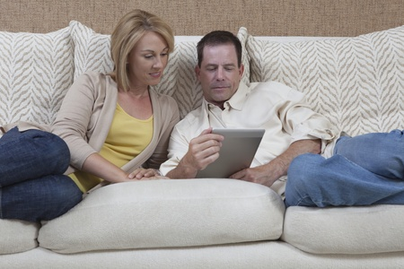Couple sit reading a digital book Stock Photo - 12738298