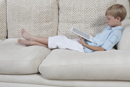 I ragazzi si siede sul divano a leggere un libro digitale