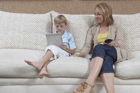 Mother and son sit on sofa boy with digital book Stock Photo - 12738301