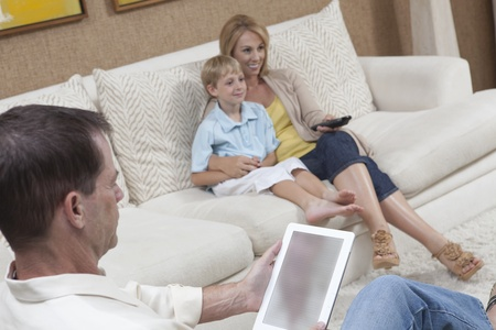 Mother and son watch television while man reads a digital book Stock Photo - 12738302
