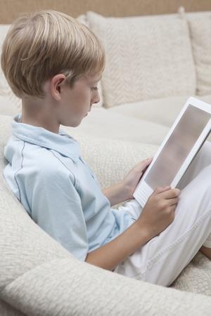 Boy lit un livre numérique Banque d'images