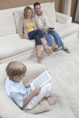Parents watch television while son reads a digital book Stock Photo - 12738307