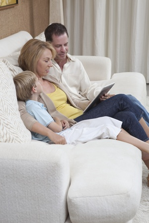 Family of three sit reading a digital book Stock Photo - 12738308