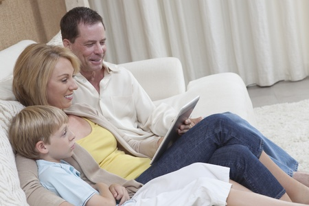 Family of three sit reading a digital book Stock Photo - 12738309
