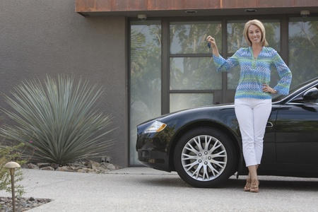 Woman stands holding keys to luxury vehicle