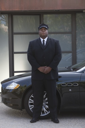 Chauffeur: Chauffeur stands with hands clapsed at luxury vehicle