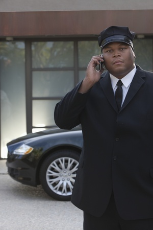 Chauffeur stands on mobile phone with luxury vehicle Stock Photo - 12738314