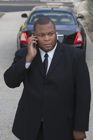 Chauffeur stands on mobile phone with luxury vehicle Stock Photo - 12738317