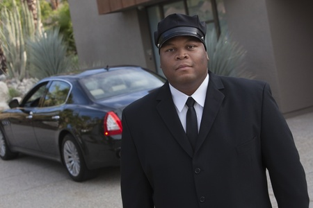 Chauffeur: Chauffeur stands in uniform with luxury vehicle