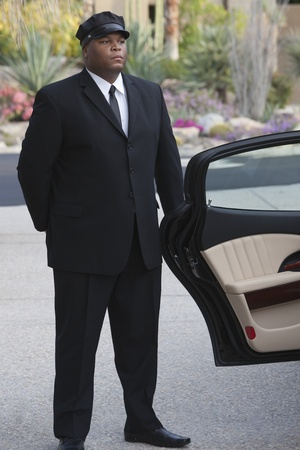 deference: Chauffeur stands at open car door of luxury vehicle