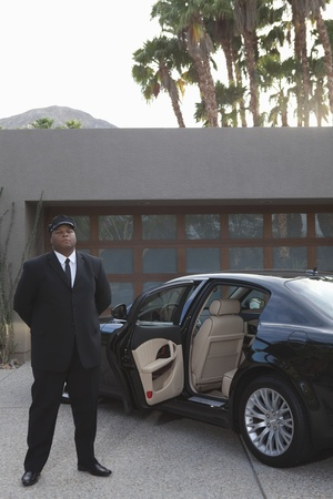 car driver: Chauffeur stands at open car door of luxury vehicle