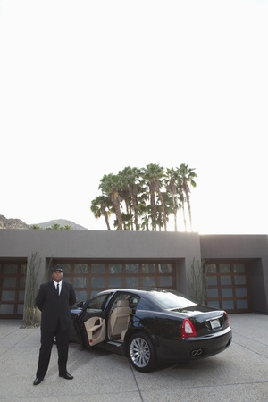 Chauffeur stands at open car door of luxury vehicle Stock Photo - 12738321