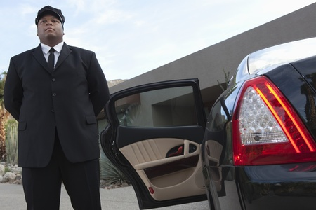 Chauffeur stands at open car door of luxury vehicle Stock Photo - 12738322