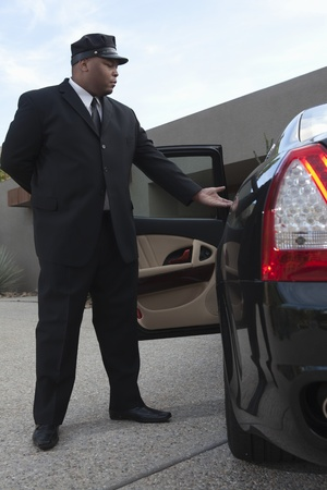 offering: Chauffeur extends hand to client in  luxury vehicle LANG_EVOIMAGES