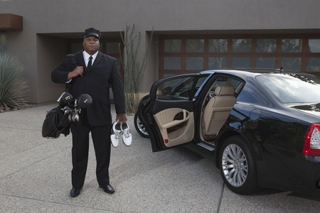 car driver: Chauffeur stands with golf equipment near luxury vehicle