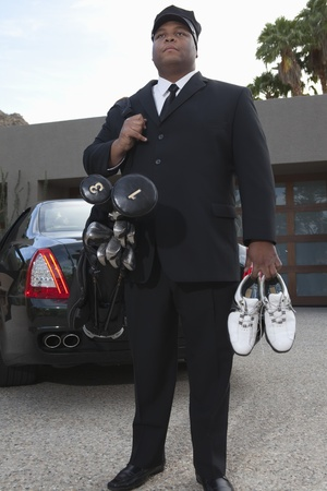 golf equipment: Chauffeur stands with golf equipment near luxury vehicle