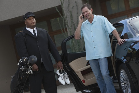 Chauffeur stands with golf equipment and owner of luxury vehicle Stock Photo - 12738326