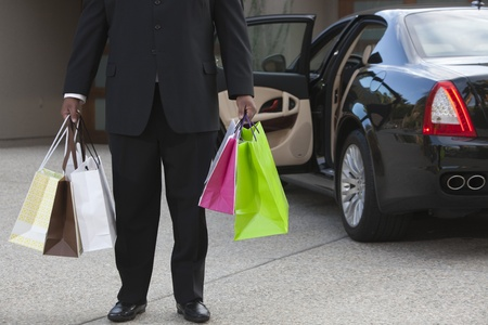 Chauffeur: Chauffeur holds shopping bags in driveway near luxury vehicle