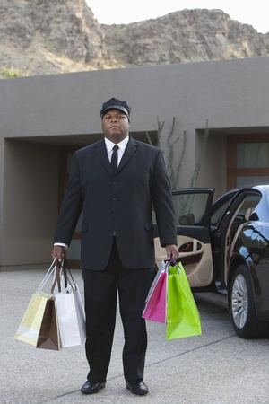 Chauffeur holds shopping bags in driveway near luxury vehicle Stock Photo - 12738333