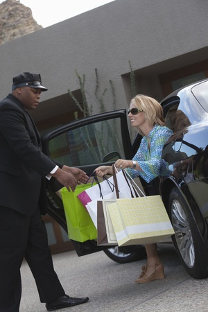 Chauffeur helps woman from luxury vehicle Stock Photo - 12738334