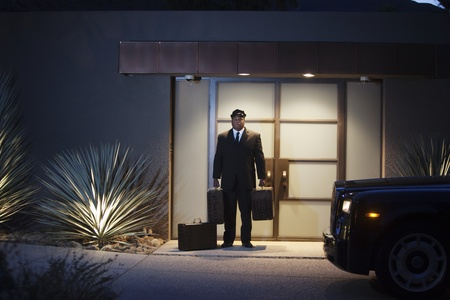 Chauffeur stands at lit entrance doorway with luggage Stock Photo - 12738336