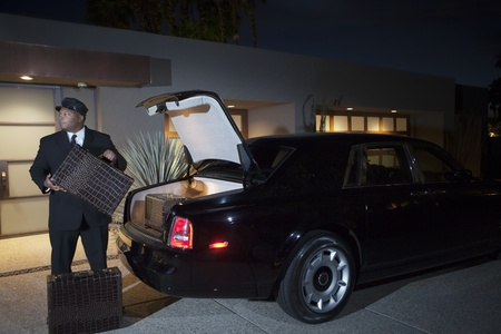 Chauffeur loads suitcases into luxury car at night Stock Photo - 12738338
