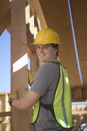 Labourer positioning plank of wood Stock Photo - 12738384