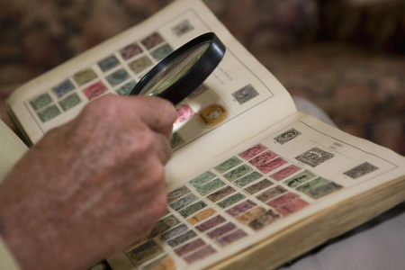 coletor: Senior man looks at stamp collection with magnifying glass