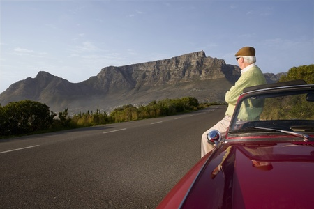 Senior man admires view leaning on vintage racing car on Signal Hill  Cape Town  South Africa Stock Photo - 12738409