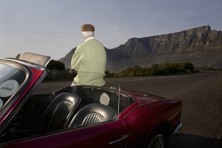 Senior man admires view leaning on vintage racing car on Signal Hill  Cape Town  South Africa Stock Photo - 12738410